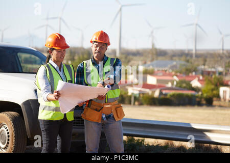 Engineers reviewing blueprints near wind turbine farm - Stock Photo