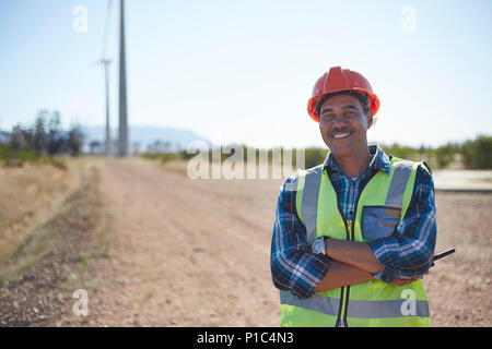 Portrait smiling engineer on dirt road at wind turbine power plant - Stock Photo