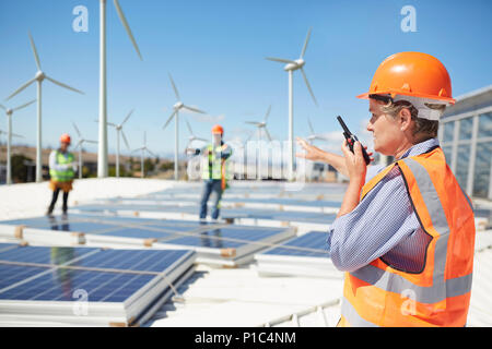 Female engineer using walkie-talkie at alternative energy power plant - Stock Photo