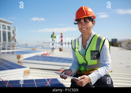 Portrait smiling, confident female engineer with digital tablet inspecting solar panels at sunny power plant