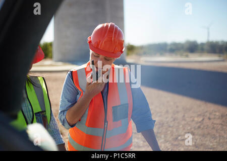 Female worker using walkie-talkie at power plant - Stock Photo