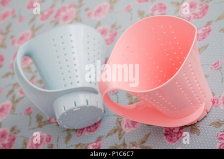 Colorful plastic colanders with handles on blue and pink floral pattern - Stock Photo