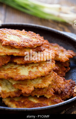 Classic Ukrainian dish deruny, potato pancakes in cast iron skillet on rustic wooden table - Stock Photo