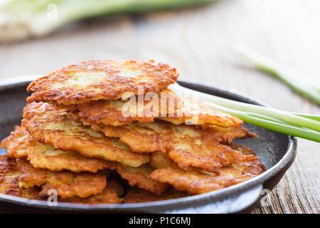 Classic Ukrainian dish deruny, potato pancakes in cast iron skillet on rustic wooden table - Stock Photo