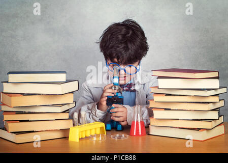 boy is making science experiments on gray background - Stock Photo