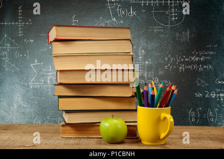 Composite image of stack of books by colored pencils in mug and apple on table - Stock Photo