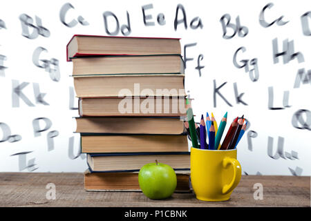 Stack of books by colored pencils in mug and apple on table - Stock Photo