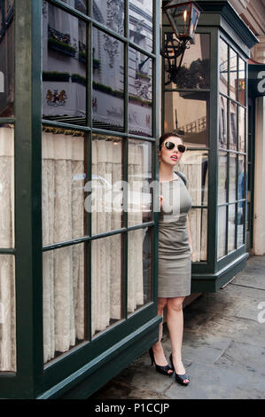 A woman standing in front of a  restaurant on Royal Street in New Orleans. - Stock Photo
