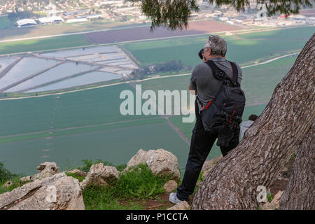 A man with a backpack is standing on Mount Gilboa in Israel and taking pictures of the A man with a backpack is standing on Mount Gilboa in Israel and - Stock Photo