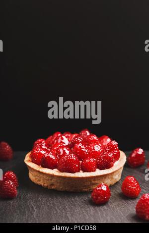 Tartlet with custard, fresh glazed raspberries, served on vintage stone surface. Dark rustic style. - Stock Photo