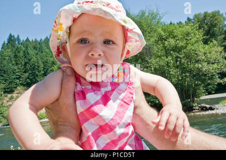 A father holding a crying 11 month old baby outdoors. - Stock Photo