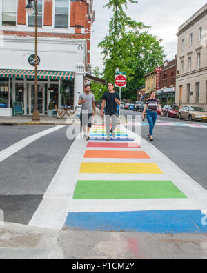 Three people cross the street, outside the Hudson Valley LGBTQ Community Center in Kingston, New York, the crosswalks are painted with the colors of the gay pride and transgender flag, and the original gay pride flag sporting eight colors flies outside the headquarters - Stock Photo