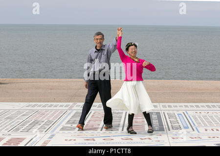 Blackpool, Lancashire, UK Weather. 12/06/2018. Sunny day at the coast after a hazy start as Chinese tourists, residents and holidaymakers enjoy the seaside attractions of the seafront Tower headland. This elderly couple from China brought a change of clothes and then waltzed on the comedy pavement to send a video back home to Asia. Credit:MediaWorldImages/AlamyLiveNews. - Stock Photo