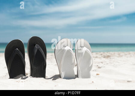 Two pair of white and blackn flip-flops in the sand. Summer vacation concept. - Stock Photo