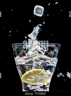 Ice Cubes dropping into  glass of water creating a splash - Stock Photo
