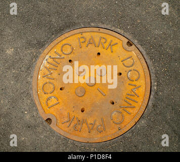 Branded manhole in Domino Park in the Williamsburg neighborhood of Brooklyn in New York on Sunday, June 10, 2018. Occupying the site of the Domino Sugar Co. refinery, closed in 2004, the five-acre greenspace has water features, slides, an elevated walkway, a Danny Meyer food stand and volleyball as well as many other amenities. Designed by James Corner Field Operations, the architects behind the design of the High Line, the brick refinery building, which at one time processed 50 percent of all the sugar in the U.S. remains for development. (© Richard B. Levine) - Stock Photo