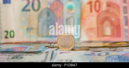 Financial dominance: One Euro in a vice against the background of the American Dollar and Euro with space for text. - Stock Photo