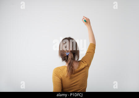 A european woman writing something isolated on white background. - Stock Photo