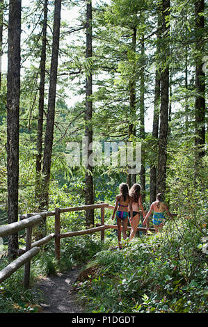 A group of girls walking on the trail above the Three Pools, swimming hole area in Oregon. - Stock Photo