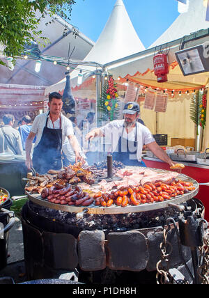 Madrid, Spain - May 15, 2018. Hispanic cooks cooking Sausages Pork Spare Ribs and others meats on a charcoal bbq in a stall of a Street Food fair. - Stock Photo