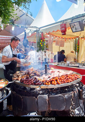 Madrid, Spain - May 15, 2018. Hispanic cook cooking Sausages, Pork Spare Ribs and others meats on a charcoal bbq in a stall of a Street Food fair. - Stock Photo