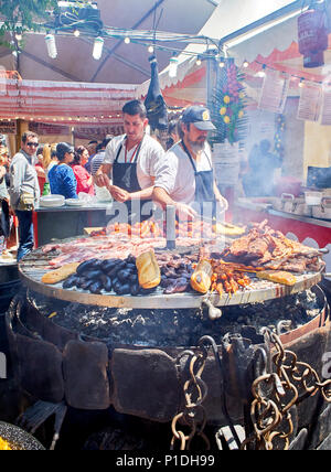 Madrid, Spain - May 15, 2018. Hispanic cooks cooking Sausages, Pork Spare Ribs and others meats on a charcoal bbq in a stall of a Street Food fair. - Stock Photo