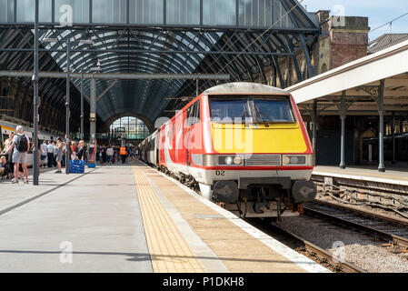 Passengers boarding a Virgin East Coast service at London Kings Cross. The UK Government has now taken control of this privatized route. - Stock Photo