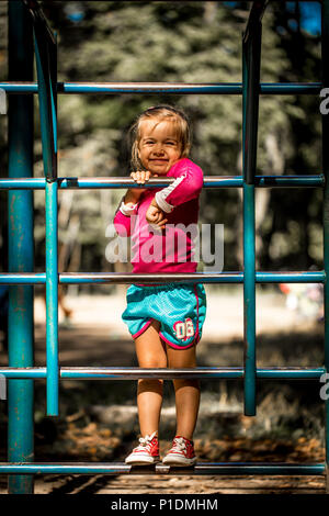 beautiful little girl playing on children's sports trainers climbs the stairs on a summer day, the emotions of a child - Stock Photo
