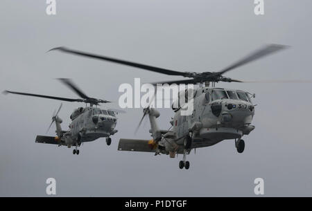 Japanese UH-60J helicopters leave to assist in simulated casualty evacuations during an amphibious warfare exercise on the DDH Type Hyuga while underway in the Pacific Ocean, May 19, 2018. Marines and Sailors with Combat Logistics Battalion 31, 31st Marine Expeditionary Unit, joined the Japan Ground Self-Defense Force service members to embark with the newly formed Amphibious Rapid Deployment Brigade to enhance the ARDB's capabilities to deal with various situations on islands.  The 31st MEU, the Marine Corps' only continuously forward-deployed MEU, provides a flexible force ready to perform a - Stock Photo