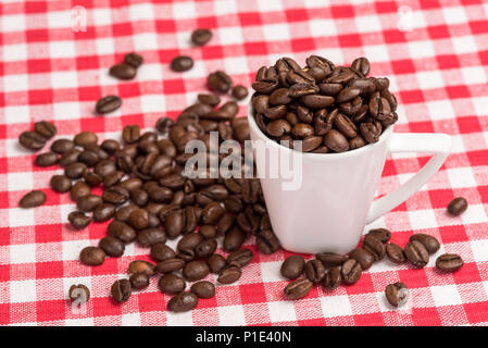 A white coffee mug is  filled with brown coffee beans. The coffee beans are also spread out on the kitchen table with a red checkered tablecloth as a  - Stock Photo