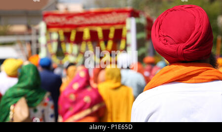 Sikh man with red turban with many people during a religious ceremony - Stock Photo