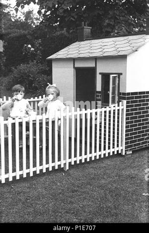 1947, summer and two young children, a little boy and girl have tea together sitting in an enclosed area outside their playhouse in a back garden, England, UK. - Stock Photo