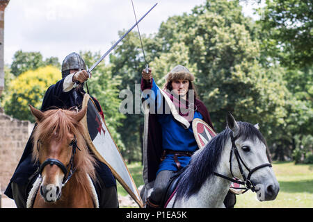 Nis, Serbia - June 10, 2018: Two knight in armor on horses and raise swords in forest. Middle ages concept - Stock Photo