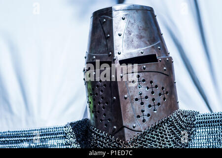 Medieval old knight helmet and chain mail for protection in battle. Very heavy headdress on stand. Middle ages armor concept - Stock Photo