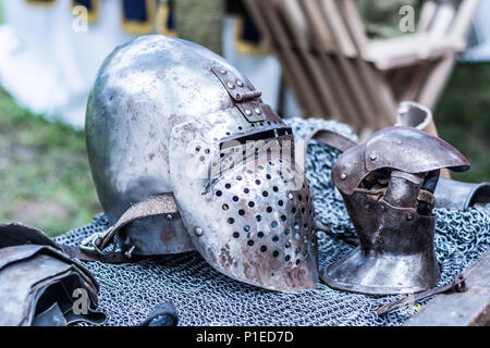 Iron helmet and protective metal glove of the medieval knight on desk with chain mail. Middle ages armor concept. Close up, selective focus - Stock Photo