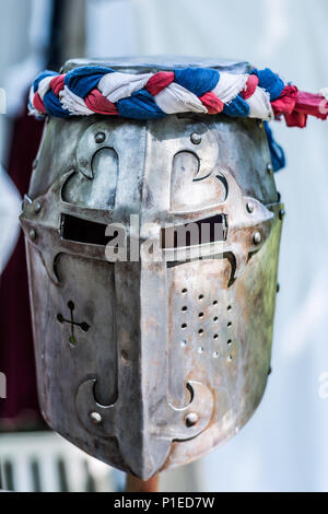 Iron helmet of the medieval knight on wooden stand with red, blue and white ribbon. Middle ages armor concept. Close up, selective focus - Stock Photo