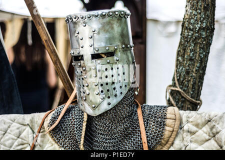 Medieval old knight helmet and chain mail for protection in battle. Very heavy headdress on stand in nature. Middle ages armor concept - Stock Photo