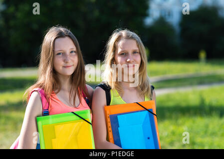 Two girls schoolgirl. Summer in nature. Tired of studying. No strength to learn anymore. In the hands of folder with notebooks. He rests after school. Best girlfriends. - Stock Photo