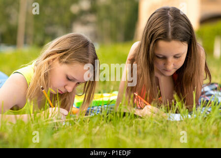 Two girls are students. Young Teens. Do the lessons write in a notebook in the summer on grass. Camping. Fills out notes draws notebooks. Perform tasks for the school. - Stock Photo