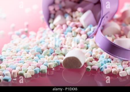 Violet pail with various marshmallows on a pink background. - Stock Photo