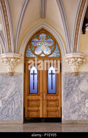Church interior door made of highly decorated oak and stained glass windows with crosses, created circa 1904 with beautiful antique craftsmanship. - Stock Photo