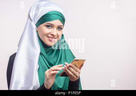 Young Muslim woman in hijab with smartphone - Stock Photo