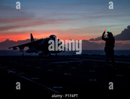 161022-N-LI768-312 PACIFIC OCEAN (Oct. 22, 2016) Chief Petty Officer Patrick Guillermo directs an AV-8B Harrier assigned to Marine Medium Tiltrotor Squadron (VMM) 163 (Reinforced) aboard the amphibious assault ship USS Makin Island (LHD 8). Makin Island, the flagship of the Makin Island Amphibious Ready Group, is deployed with the embarked 11th Marine Expeditionary Unit in support of the Navy's maritime strategy in the U.S. 3rd Fleet area of responsibility. (U.S. Navy photo by Seaman Devin M. Langer/Released) - Stock Photo