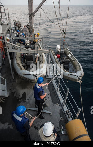 161019-N-SB587-0983    Sailors lower a 5-meter rigid-hull inflatable boat from the mine countermeasure ship USS Dextrous (MCM 13) as part of U.K./U.S. Mine Countermeasures Exercise 17-1 in the Arabian Gulf Oct. 19, 2016. The bilateral exercise serves to enhance cooperation, mutual MCM capabilities and interoperability between the U.S. and UK Naval forces in ensuring free flow of commerce, freedom of navigation and long-term regional security. Dextrous is assigned to Commander, Task Force 52 supporting mine countermeasure operations in the U.S. 5th Fleet area of responsibility. (U.S. Navy Comba - Stock Photo