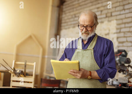 closeup photo of handsome old craftsman writing something in the notepad - Stock Photo