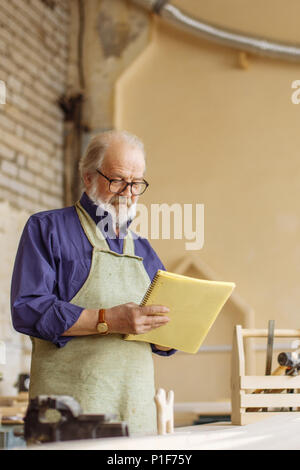 close-up side view shot of elderly man holding exercise book in his workroom - Stock Photo