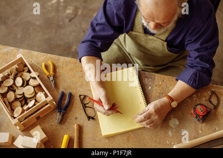 top view shot of old craftsman sitting with pencil and exercise book - Stock Photo
