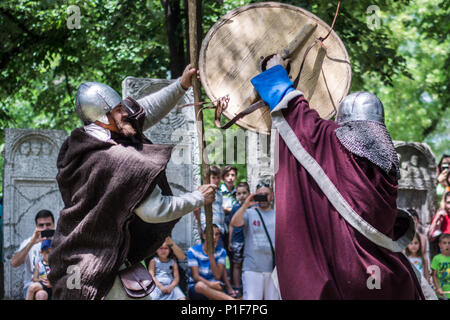 Nis, Serbia - June 10, 2018: Two knights in armor fighting in nature with old weapon. Medieval Festival battle concept - Stock Photo