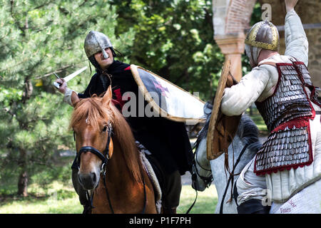 Nis, Serbia - June 10, 2018: Two medieval knight fighting with sword on horses in nature. Middle ages battle concept - Stock Photo