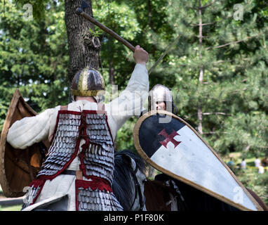 Nis, Serbia - June 10, 2018: Battle of knight on horses with swords in forest. Middle ages fighting concept - Stock Photo